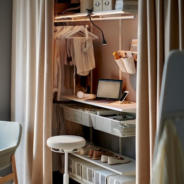 A workstation inside a white BOAXEL storage system behind curtains, with lighting and a sit/stand support.
