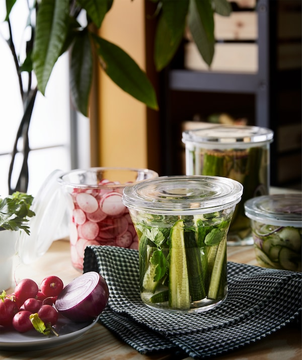 A worktop next to a window. Standing on it are several clear, lidded jars filled with pickled radishes and cucumbers.