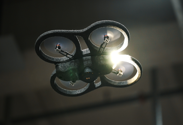 A worm's eye view of a big drone in a dark warehouse.