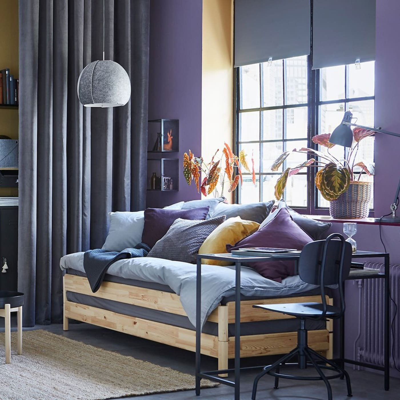 A yellow and purple studio with UTÅKER pine stackable sofa bed and IVAR wooden storage units in grey steel.