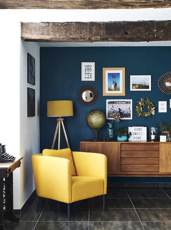 A yellow armchair against a dark blue wall in a renovated farmhouse in France.