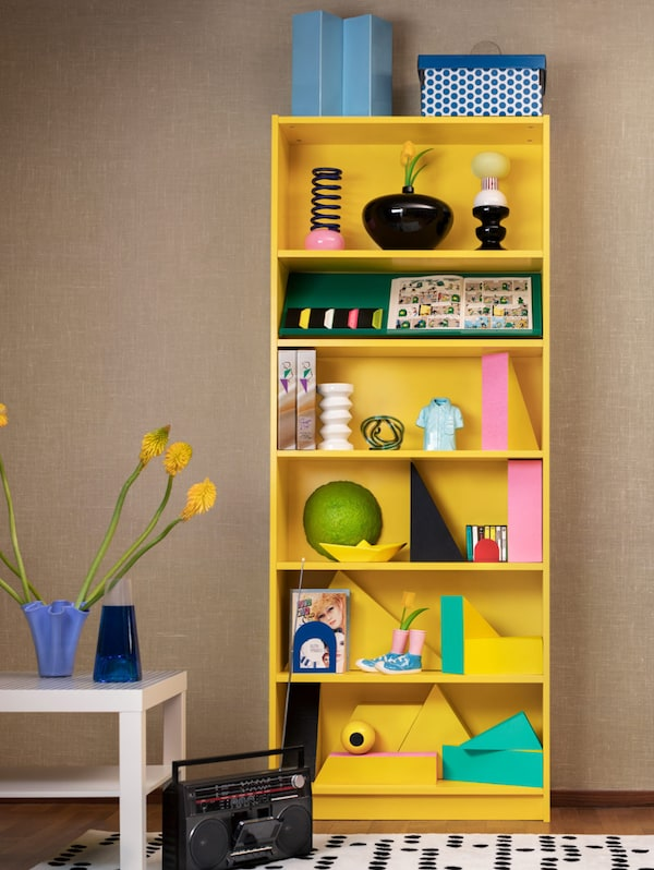 A yellow BILLY bookcase is filled with colourful miscellaneous items. Next to it is a white table and a cassette player.