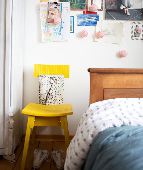 A yellow chair against a white wall decorated with pictures and notes, next to a wooden bed.