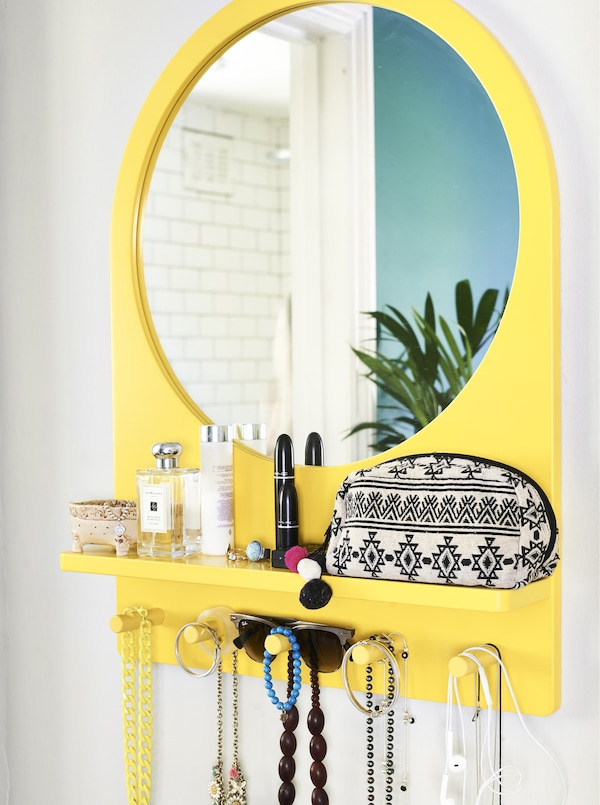 A yellow mirror with built-in pegs and shelf.