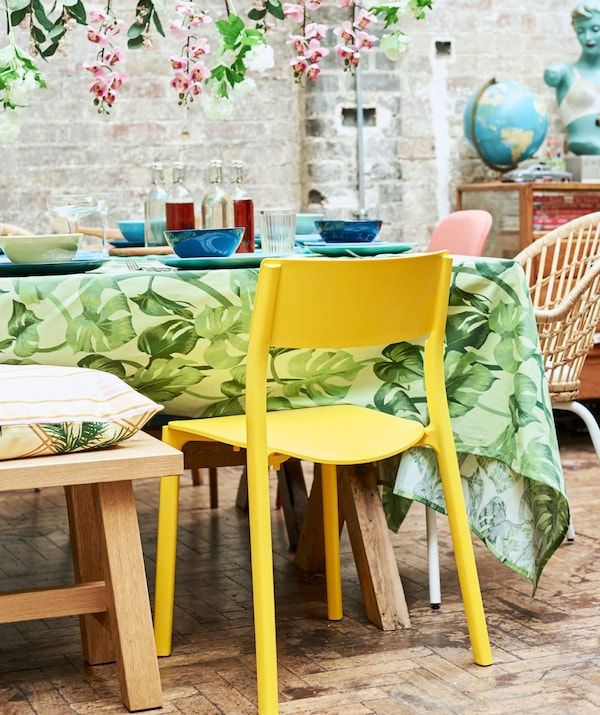 A yellow plastic dining chair pulled up to a table covered with a green leaf-print tablecloth and blue crockery.