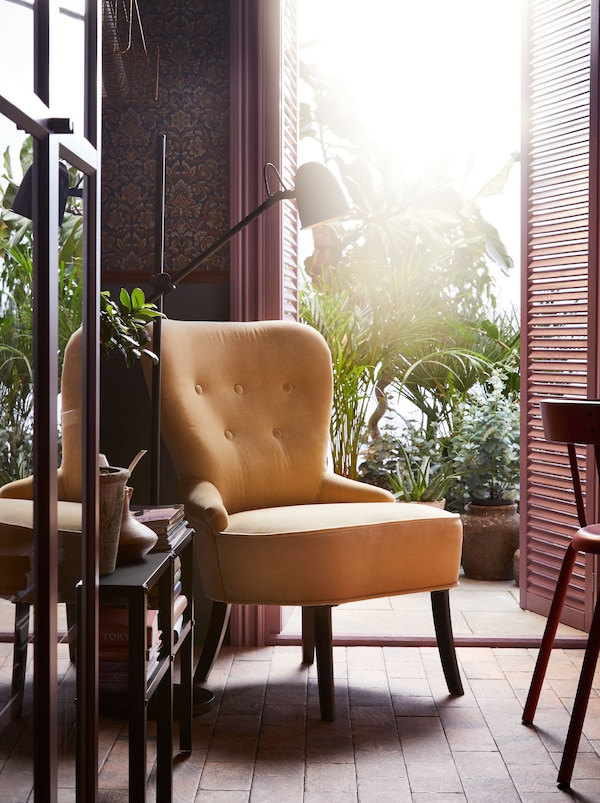 A yellow REMSTA armchair by a door opening onto a planted terrace. A black floor lamp and table with books is beside it.