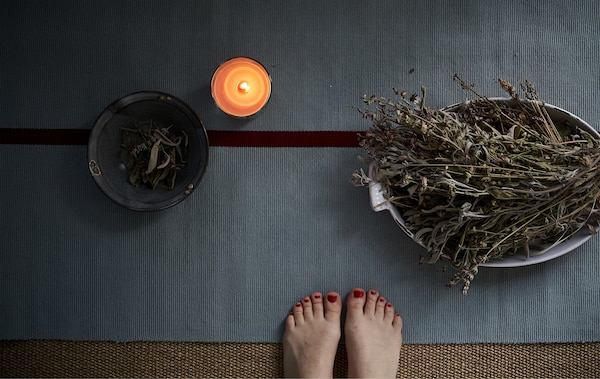A yoga mat, candle and bowls of herbs.