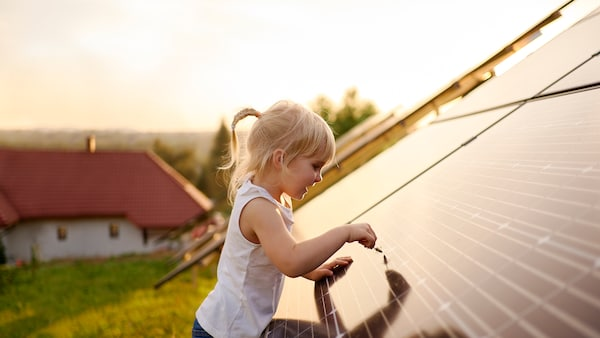A young blonde girl is touching a solar panel with a straw of grass on the roof of a house in the countryside.