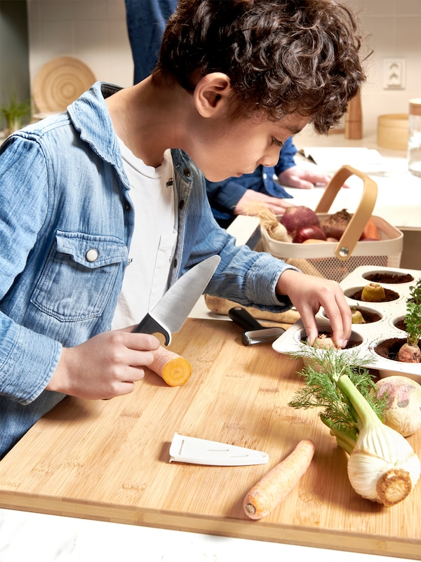 A young boy holding a knife and placing a carrot top in a baking tray full of soil on a wooden surface with other vegetables.