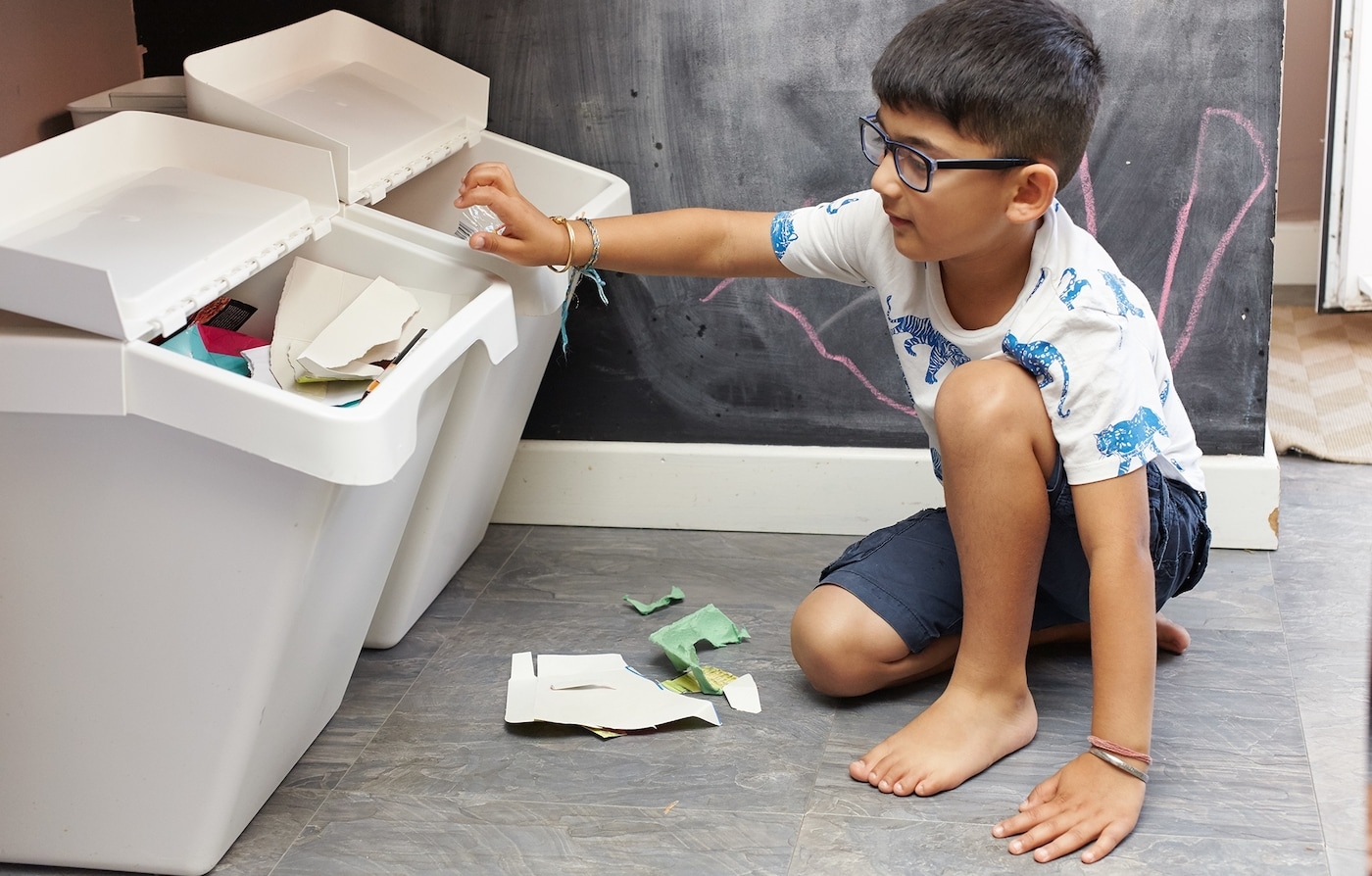 A young boy is sitting on the floor and recycling cardboard in white sorting bins.
