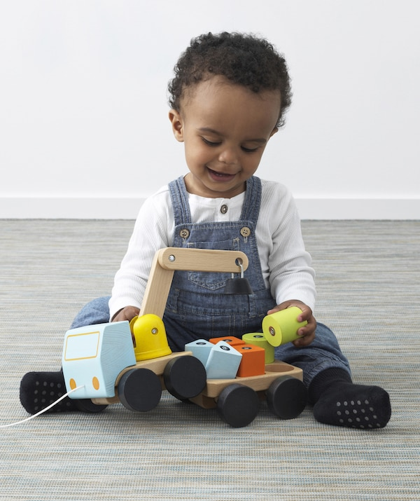 A young child plays with a wooden crane and blocks.