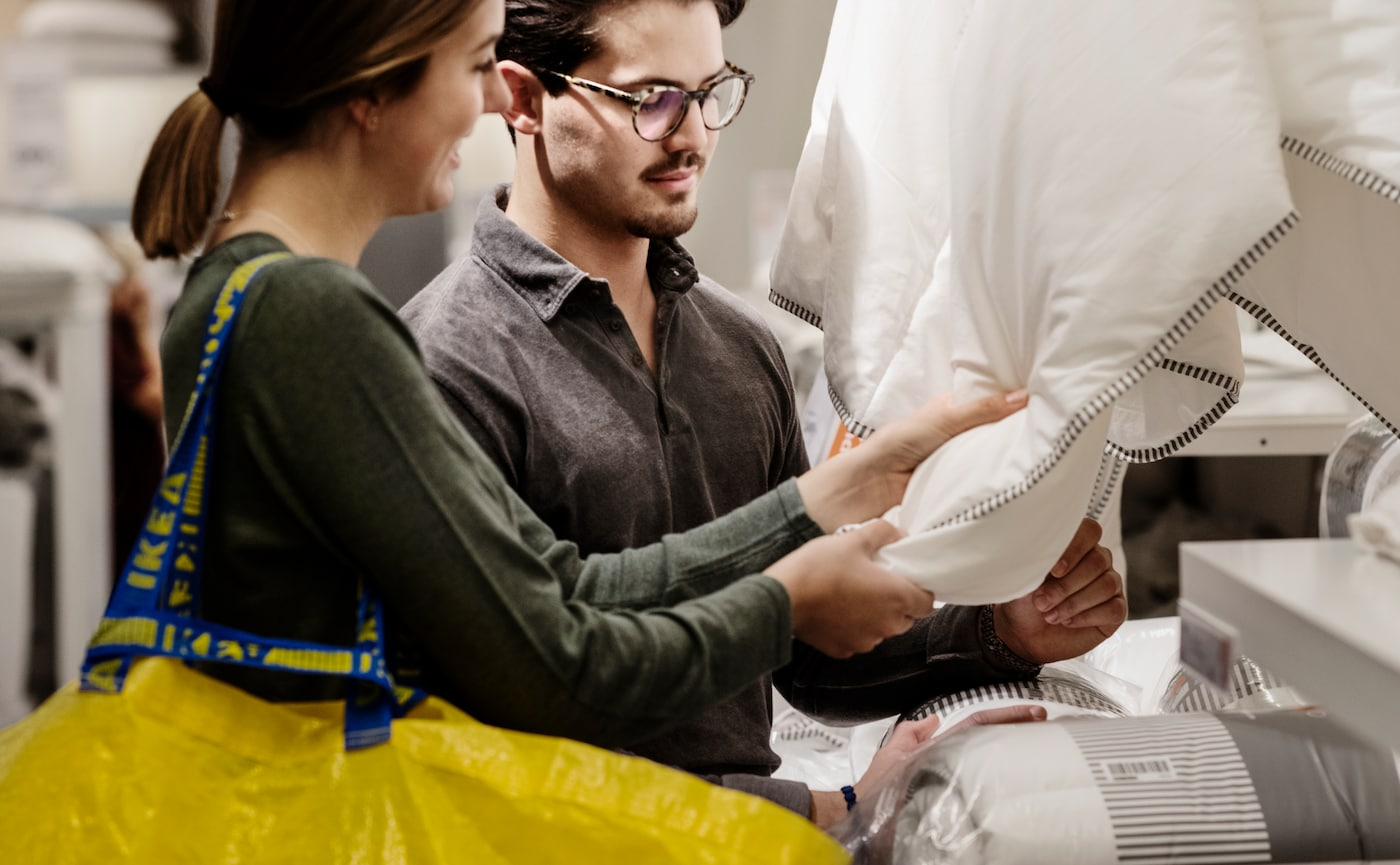A young couple are exploring the hand feel of a duvet while shopping at an IKEA store.