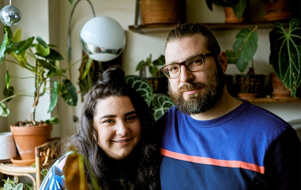 A young couple in their urban apartment with lots of plants behind them.