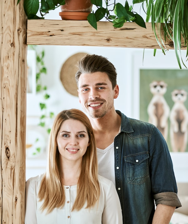 A young couple stand next to wood beams with framed illustrations on the wall behind them.