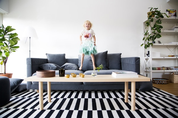 A young girl bouncing on a sofa in front of a coffee table in the living room.