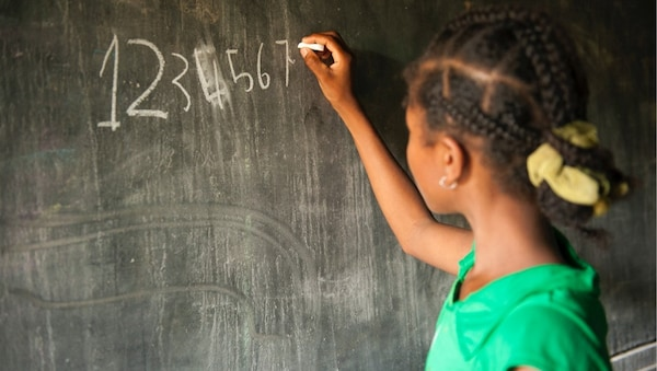 A young girl facing a chalkboard writing her numbers on the board from 1 to 7