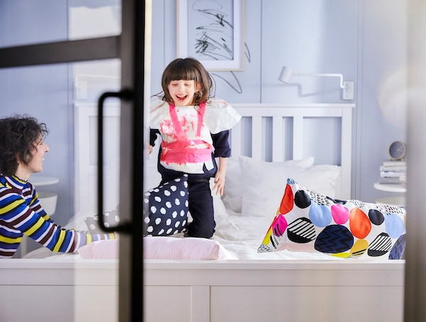 A young girl jumping on a white double bed.