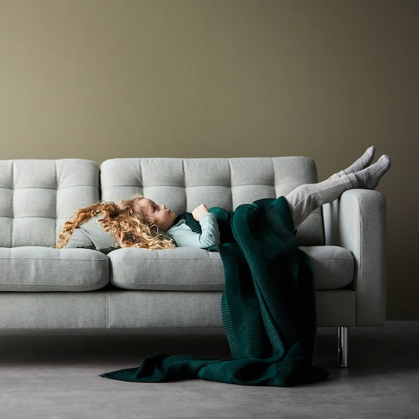 A young girl lying on a sofa with ler legs on the armrest and a green blanket covering her.