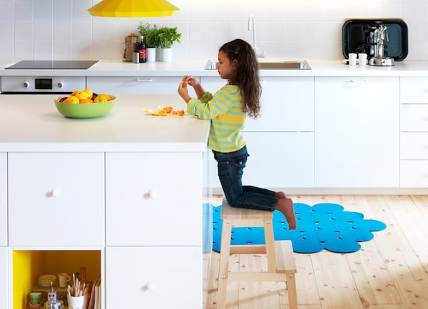 A young girl peels an orange in a white kitchen