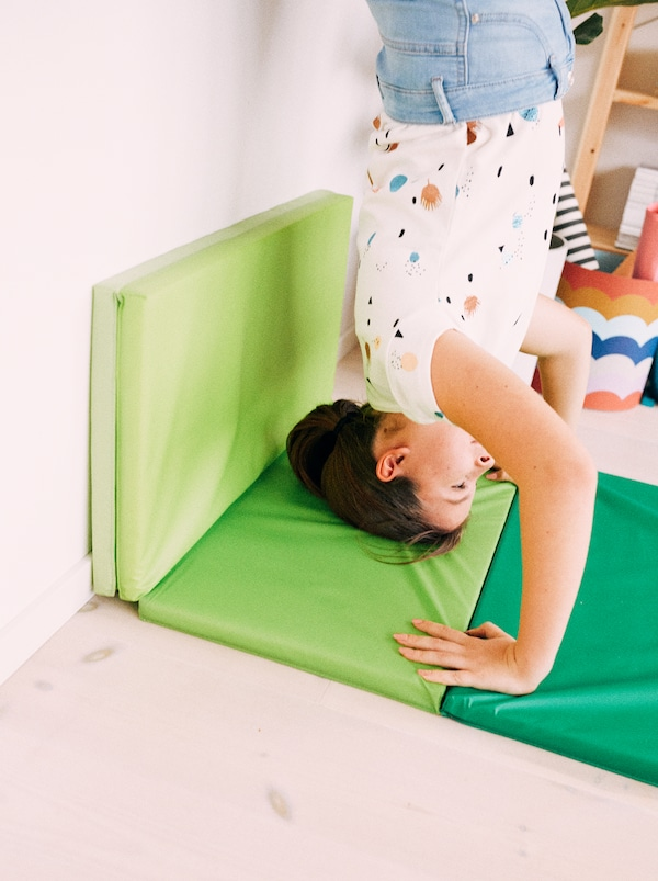 A young girl performs a handstand against a wall, her head and arms supported by a bright green PLUFSIG folding gym mat.