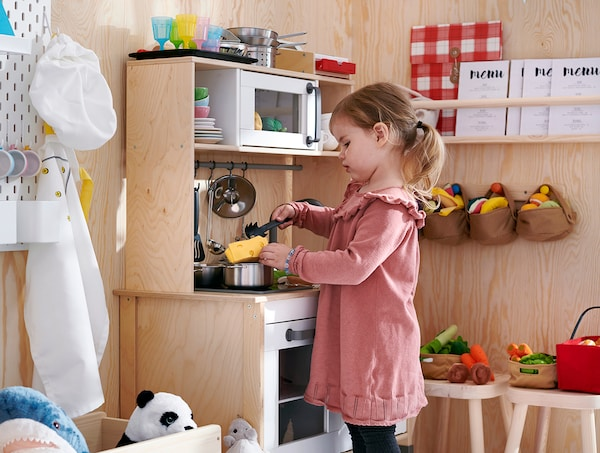 A young girl playing with a DUKTIG birch play kitchen.