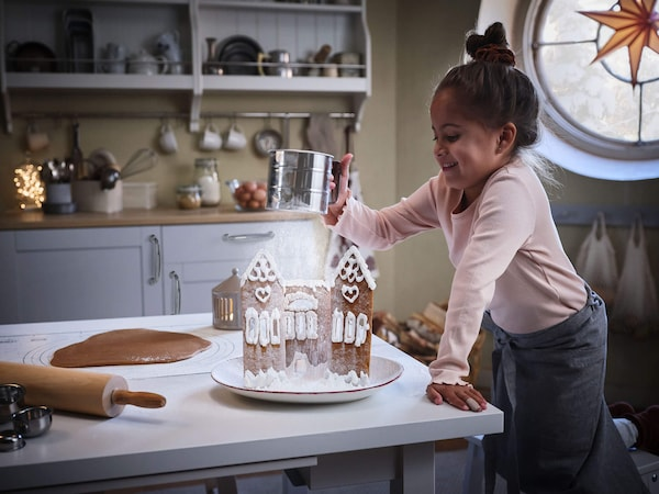 A young girl sifting powdered sugar on a gingerbread house in a kitchen.