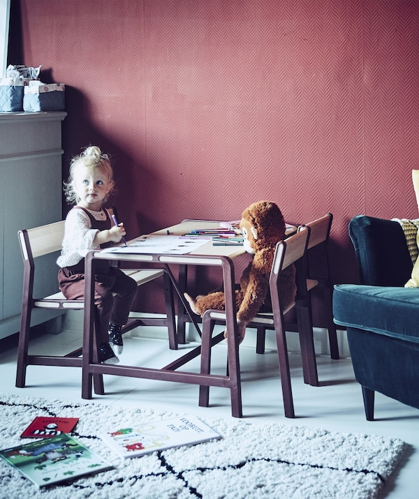 A young girl sitting at a children's table in a red room.