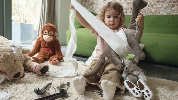 A young girl sitting wrapping up a soft toy in toilet paper with other soft toys sitting near her.