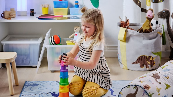 A young girl stacking colourful toys into a tower.