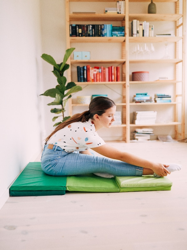 A young girl stretches while sat on a green PLUFSIG folding gym mat, with a plant and IVAR shelf in the background.