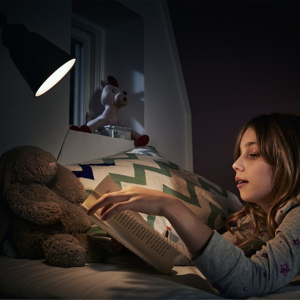 A young girl, wearing a grey sweater, lying in bed and reading a book under a bright light.