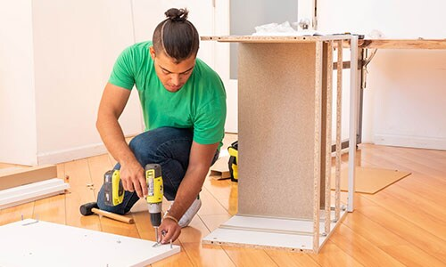 A young man assembling IKEA furniture.