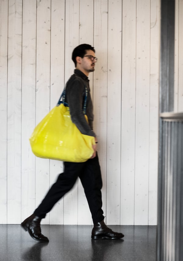 A young man dressed in black walking around in an IKEA store carrying a yellow shopping bag.
