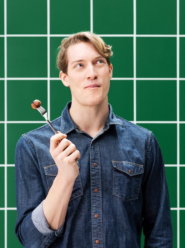 A young man in a denim shirt looking upwards while tasting a plant ball and holding a fork with another plant ball.