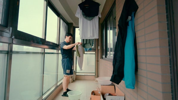 A young man is hanging washed clothes to dry in an enclosed brick and glass wall balcony.