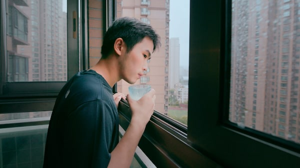 A young man is holding a glass of water while looking out of an apartment window.