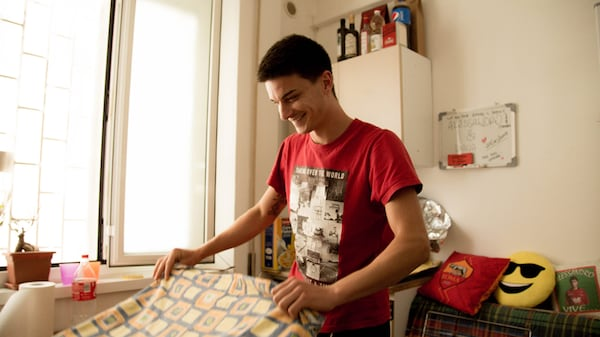 A young man is putting a cloth on a kitchen table in his apartment.