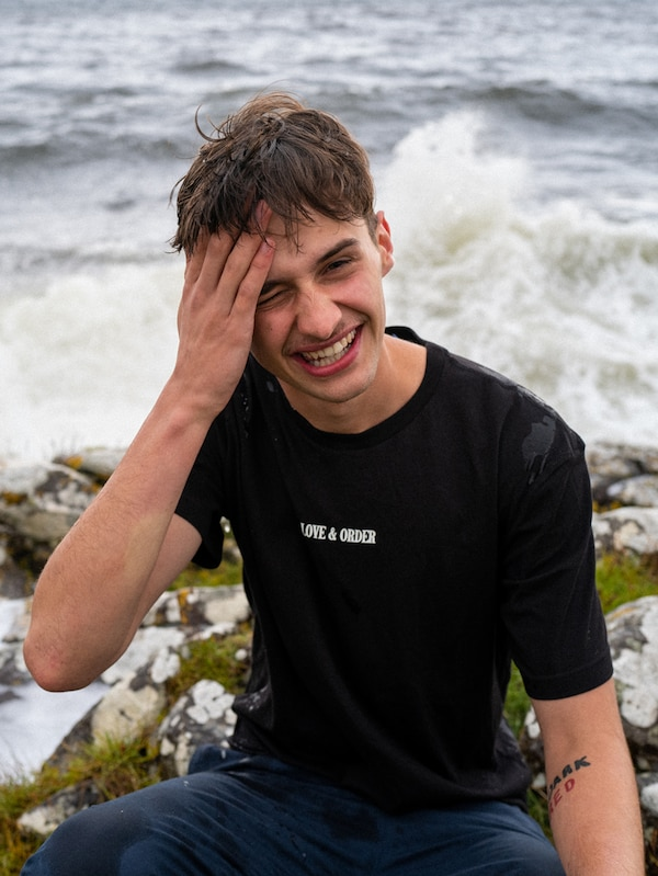 A young man wearing a black t-shirt is sitting by the ocean on a rock, laughing. Waves are crashing behind him.