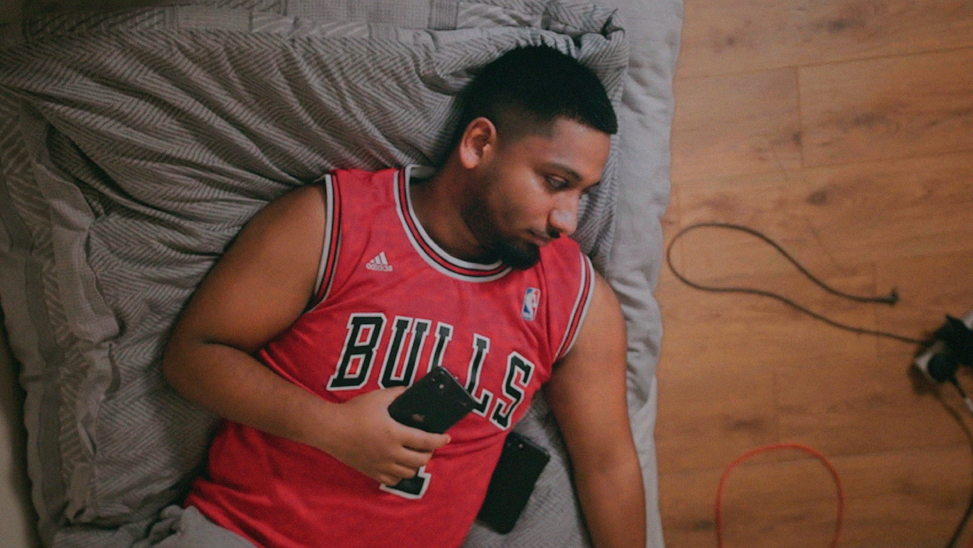 A young man with a beard and a red sports shirt is relaxing on a grey sofa while holding a phone.