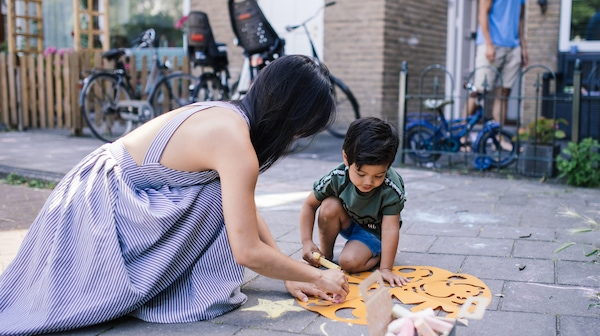 A young woman in a dress and a little boy in a t-shirt and shorts are playing with crafts on the street outside a house.