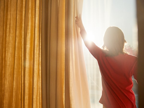 A young woman in a red T-shirt pulling back a yellow curtain to greet the sun from her balcony.