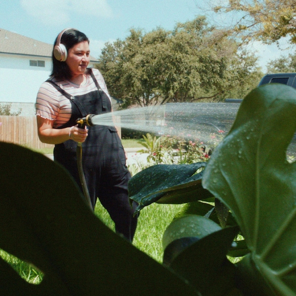 A young woman in dungarees is wearing headphones and holding a water hose, watering a large garden plant.