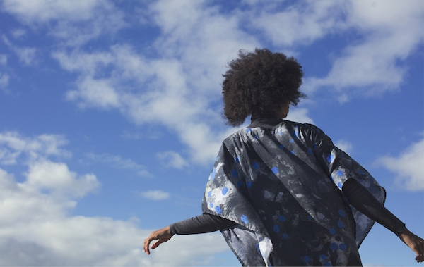 A young woman outdoors wearing a patterned black, blue and white kaftan from the IKEA ANNANSTANS collection.
