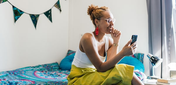 A young woman wearing bright yellow pants and a pair of glasses is sitting on her bed. She is smiling at her phone.