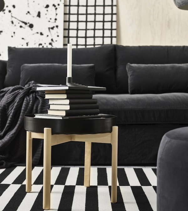 A YPPERLIG black topped coffee table with four birch legs, stacked with black books and a YPPERLIG black candleholder.