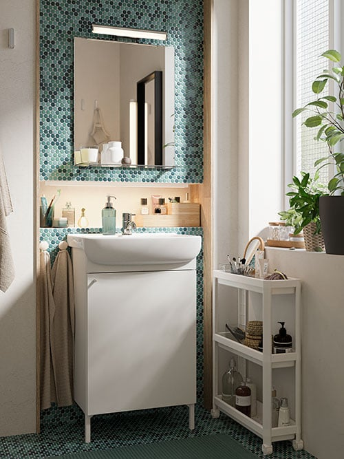 A Zen-inspired green-tiled bathroom, vanity cabinet, mirror with shelf, white cart and plants on a windowsill.