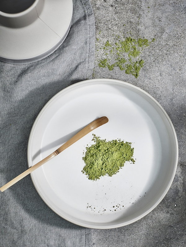 The handmade HANTVERK bowl from above, with green matcha powder – made by artisans in Thailand.