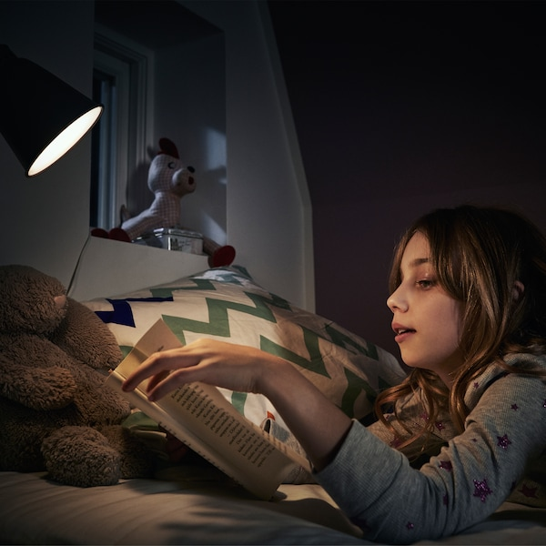A girl with long brown hair lays on her stomach in bed and reads a book under the light of a wall lamp.