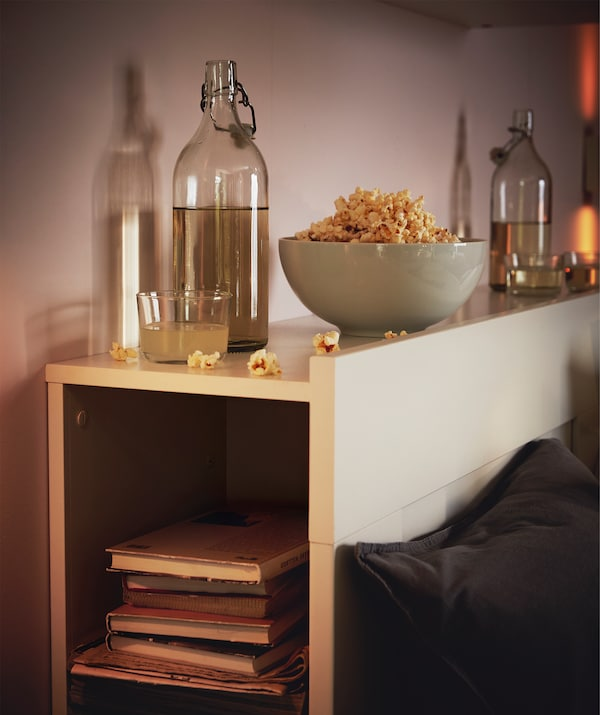 Headboard of a bed that doubles as a shelf; a pile of books in the hollow, filled glass bottles and snack bowl on top.