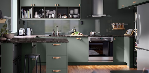 Green cabinets with light stained wood flooring and stainless steel appliances